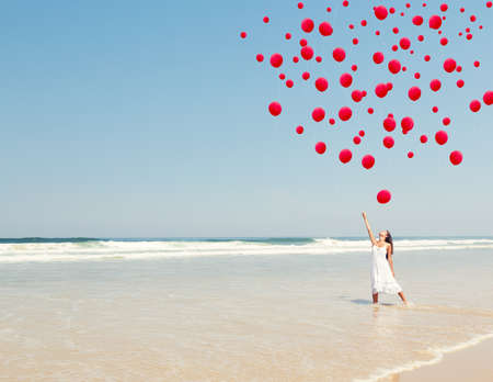 Beautiful girl in the beach dropping red ballons in the sky photo