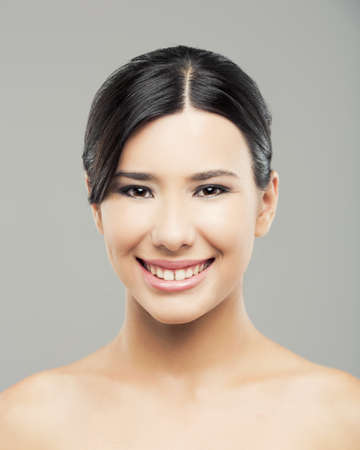 Beauty portrait of young asian woman smiling, over a gray background. Stock Photo - 17903524