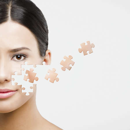 people puzzle: Beauty concept of a beautiful Asian woman with puzzle pieces in the face
