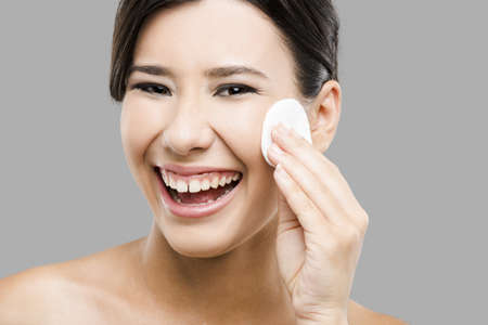 Beauty portrait of an Asian young woman cleaning the face with cotton Stock Photo - 17903514