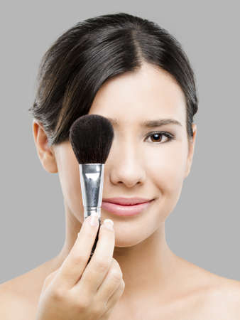 Beauty portrait of an Asian young woman holding make-up brushes Stock Photo - 17903501