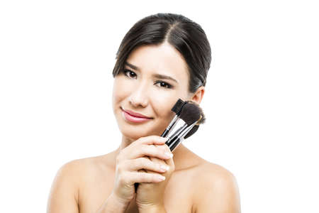 light complexion: Beauty portrait of an Asian young woman holding make-up brushes