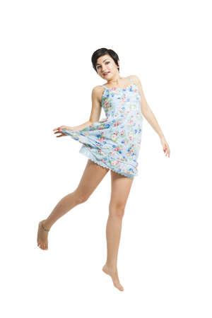 Beautiful teenager with a blue dress dancing and jumping, isolated over white background Stock Photo - 17903497