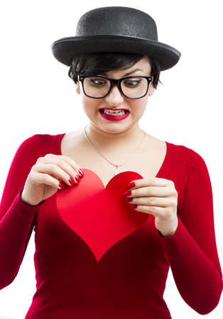 Beautiful and funny nerd girl ripping a paper heart,  isolated on white background Stock Photo - 17903529