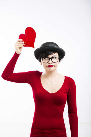 Beautiful  and funny nerd girl, holding a heart over her head, aganist a white background Stock Photo - 17903528