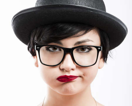 Close-up portrait of a beautiful girl bored with something, wearing a hat and nerd glasses Stock Photo - 17903510