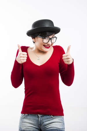 Beautiful girl wearing a hat and nerd glasses and thumbs up, isolated on white Stock Photo - 17903526
