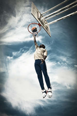 A basketball player drives to the hoop for a slam  photo