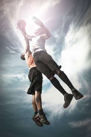 Two Basketball players playing street basket and jumping together to catch the ball photo