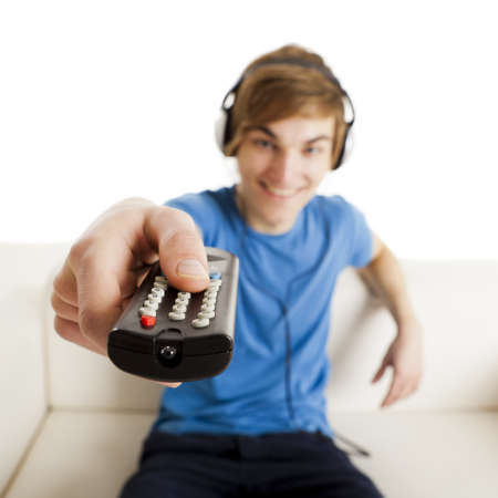 Young man sitting on the couch using a remote control Stock Photo - 18293896