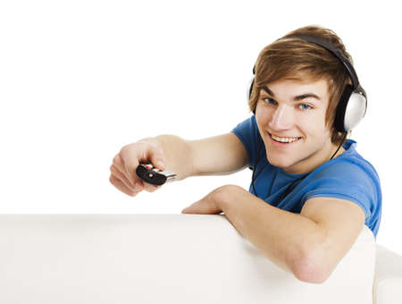 Young man sitting on the couch using a remote control, with copyspace for the designer Stock Photo - 18293903