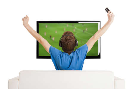 lcd tv: Young man sitting on the couch watching a football game on tv with arms up