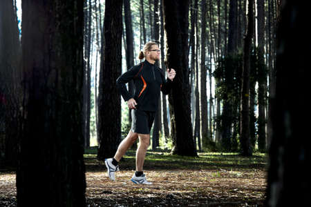 Athletic man doing exercise, running in the forest Stock Photo - 18293916