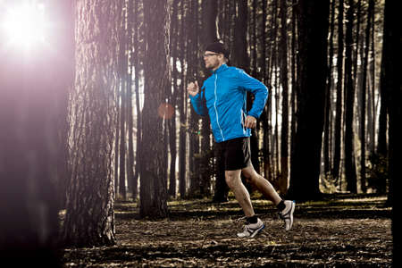 Athletic man doing exercise, running in the forest Stock Photo - 18293937