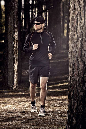 Athletic man doing exercise, running in the forest Stock Photo - 18294083