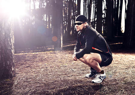 Athletic man resting after running in the forest Stock Photo - 18294107