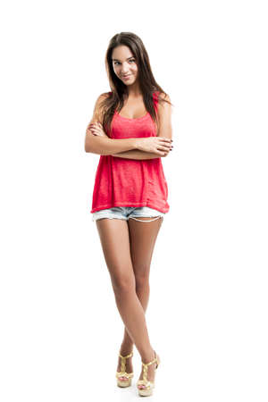Beautiful young woman standing with arms crossed over a white background photo