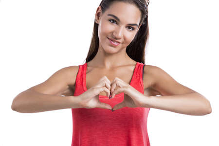 Beautiful woman making a heart symbol with her hands, isolated on white background Stock Photo - 18293917