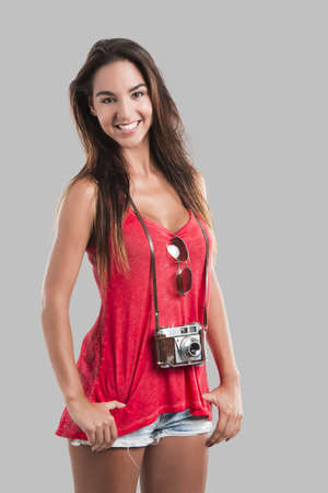 Beautiful young woman smiling and posing with a old vintage camera Stock Photo - 18293926
