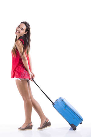 Happy woman going on vacation and walking with a suitcase Stock Photo - 18293891