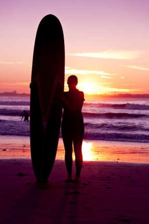 chica surf: Surfer chica con tabla de surf en la playa de la puesta Foto de archivo