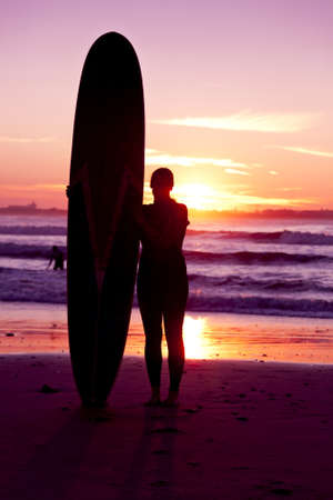 Surfer girl with surfboard at sunset beach Stock Photo - 18293905