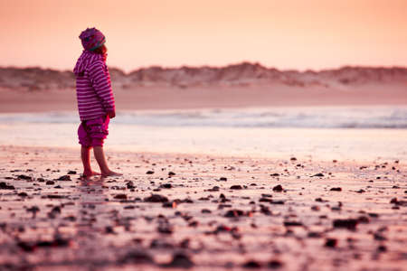 Little girl standing in the beach looking to the ocean Stock Photo - 18293910
