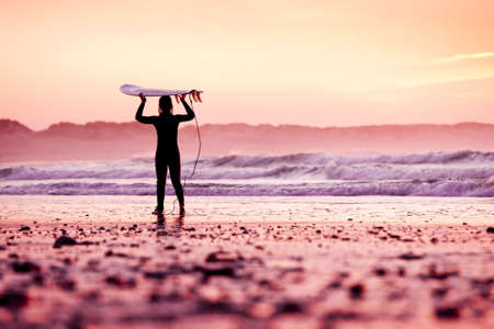 Female surfer on the beach at the sunset Stock Photo - 18293911