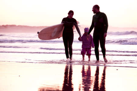 Female surfer and her familly walking in the beach at the sunset photo