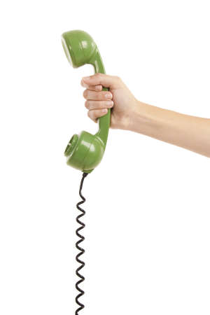 old phone: Female hand holding a green handpiece from a vintage telephone