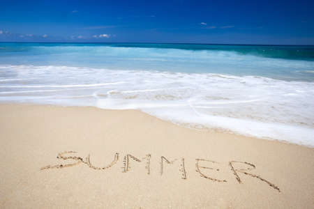 Beautiful tropical beach with the word summer written on the sand photo