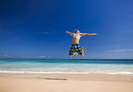Athletic young man enjoying the summer, jumping in a tropical beach photo