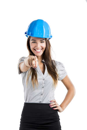 Beautiful and confident young female architect wearing a blue helmet and pointing, isolated on white photo
