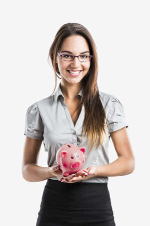 Beautiful and attractive young business woman smiling holding a piggy bank, isolated on white photo