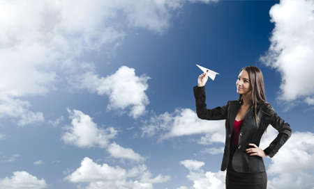 paper airplane: Beautiful business woman throwing a paper plane, against a beautiful blue sky