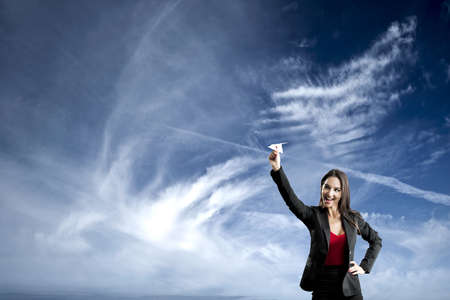 throw paper: Beautiful business woman throwing a paper plane, against a beautiful blue sky