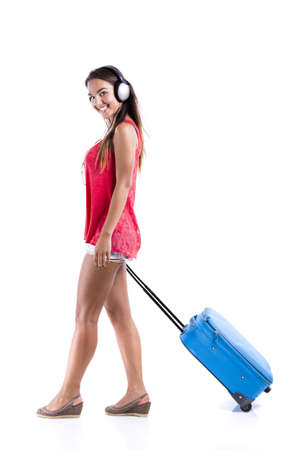 Happy woman going on vacation and walking with a suitcase while listen music photo