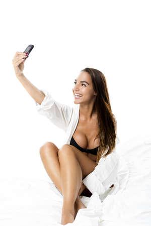 hot breast: Красивая и сексуальная женщина на кровати и сфотографировать себя, изолированных на белом фоне