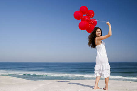 Beautiful girl with red ballons in the beach  photo