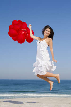 Beautiful girl jumping with red ballons in the beach  photo