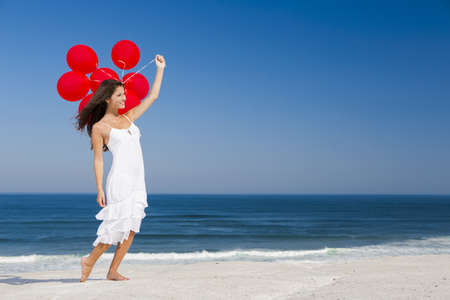 woman flying: Beautiful girl with red ballons in the beach  Stock Photo