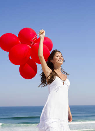Beautiful girl with red ballons in the beach and wind blowing in the face photo