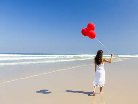Beautiful girl walking in the beach and holding red balloons photo
