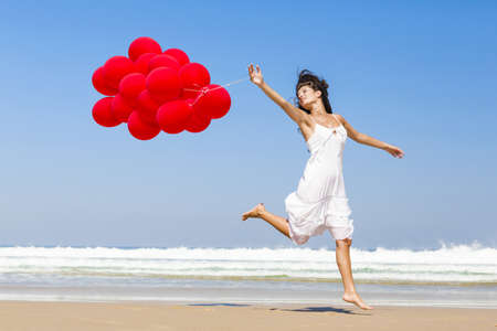 ballons: Beautiful girl walking in the beach and holding red balloons Stock Photo