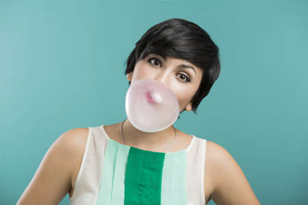 Portrait of a beautiful girl with a bubble gum on the mouth, against a blue background