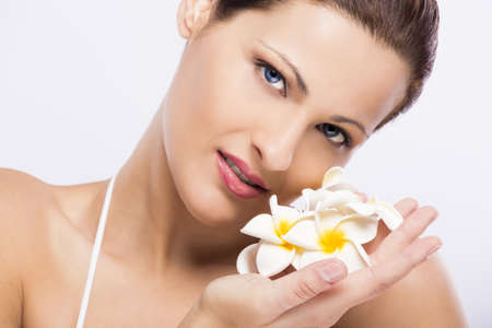 Close up portrait of a beautiful blonde woman holding plumeria flowers close to the face photo