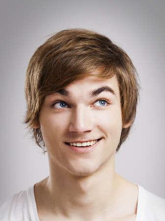 hombres jovenes: Retrato de un hombre joven y guapo, sobre un fondo gris Foto de archivo