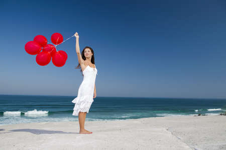 Beautiful girl with red ballons in the beach  Stock Photo - 18971903