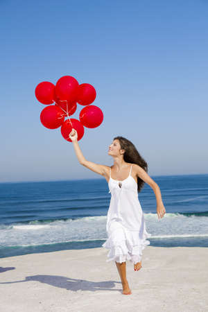 Beautiful girl running with red ballons in the beach  photo