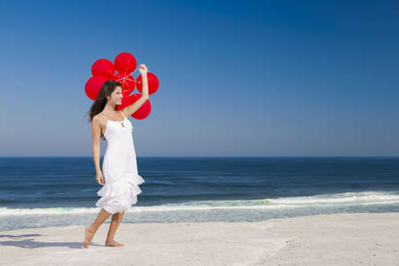 Beautiful girl with red ballons in the beach Stock Photo - 18971902
